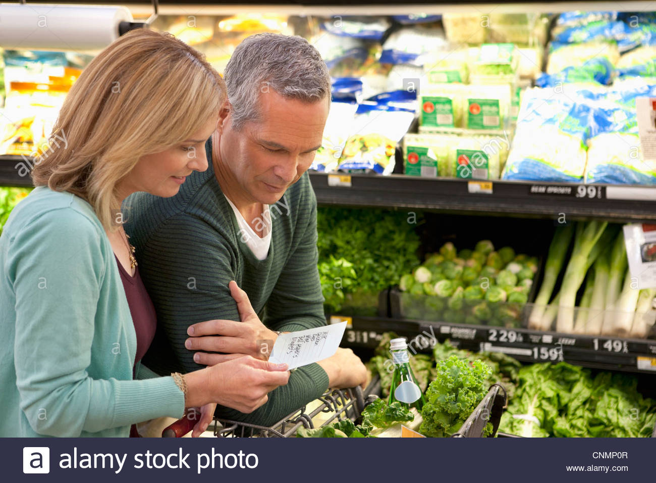 Couple checking grocery list in supermarket - Stock Image