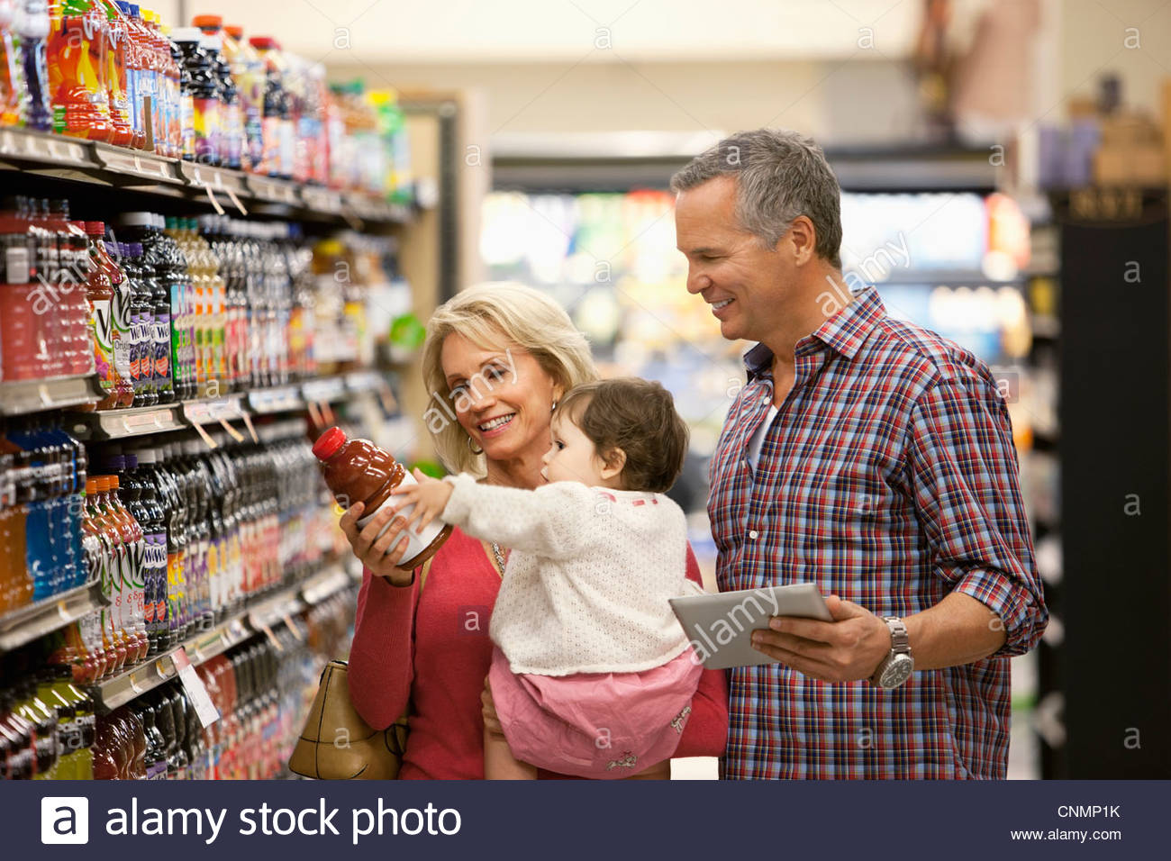 Family shopping for juice in supermarket - Stock Image
