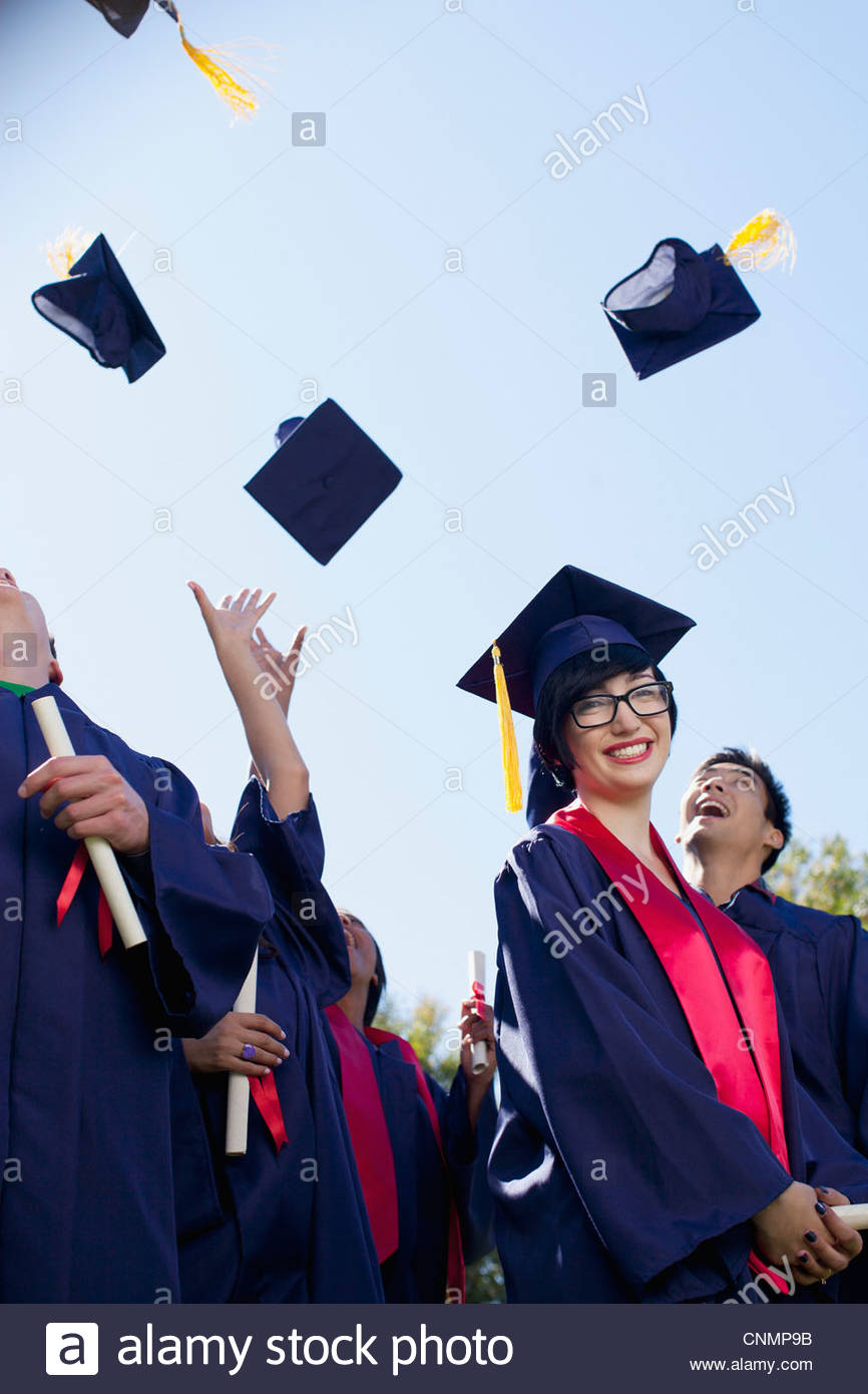 Graduates tossing caps in air outdoors - Stock Image