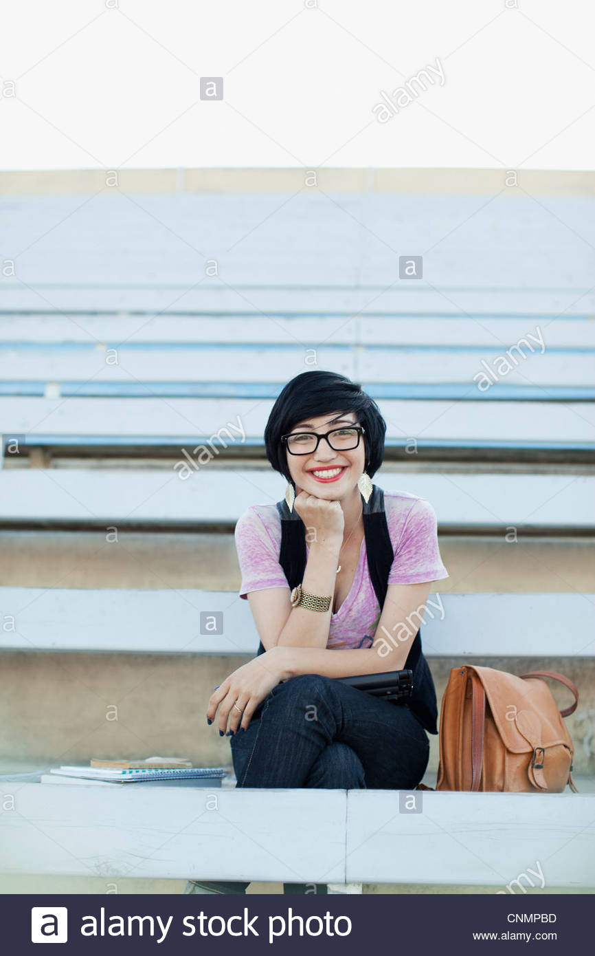 Smiling student sitting on bleachers - Stock Image