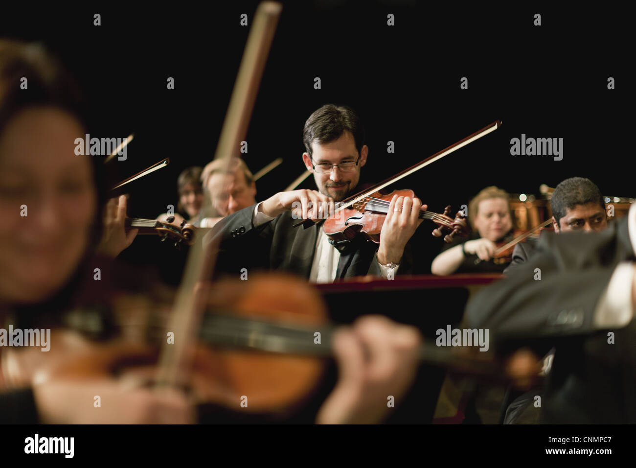 Violin players in orchestra - Stock Image