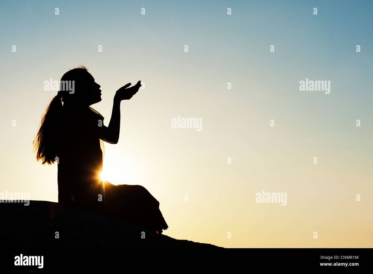 Indian girl sitting holding out her hands at sunset. Silhouette Stock Photo