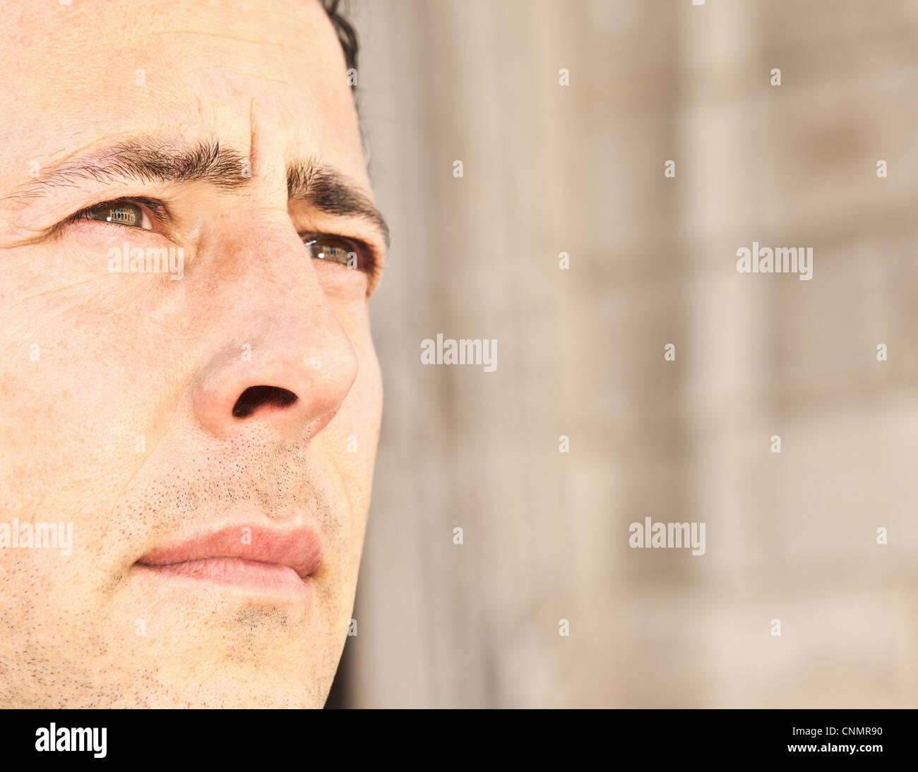 Close up of businessman's serious face - Stock Image