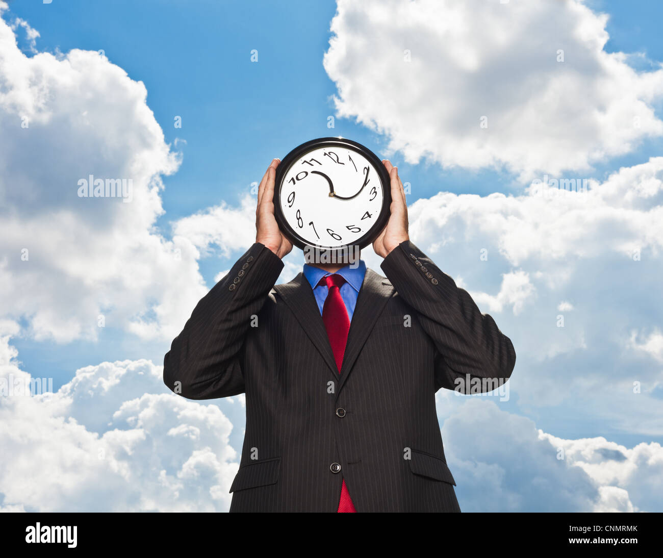 Businessman holding warped clock - Stock Image