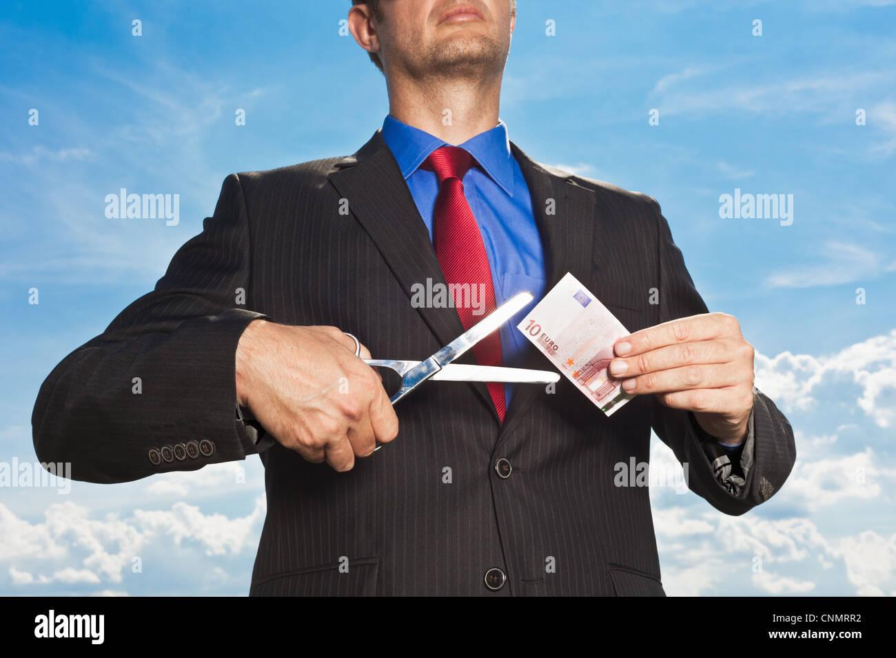 Businessman slicing Euro bill - Stock Image