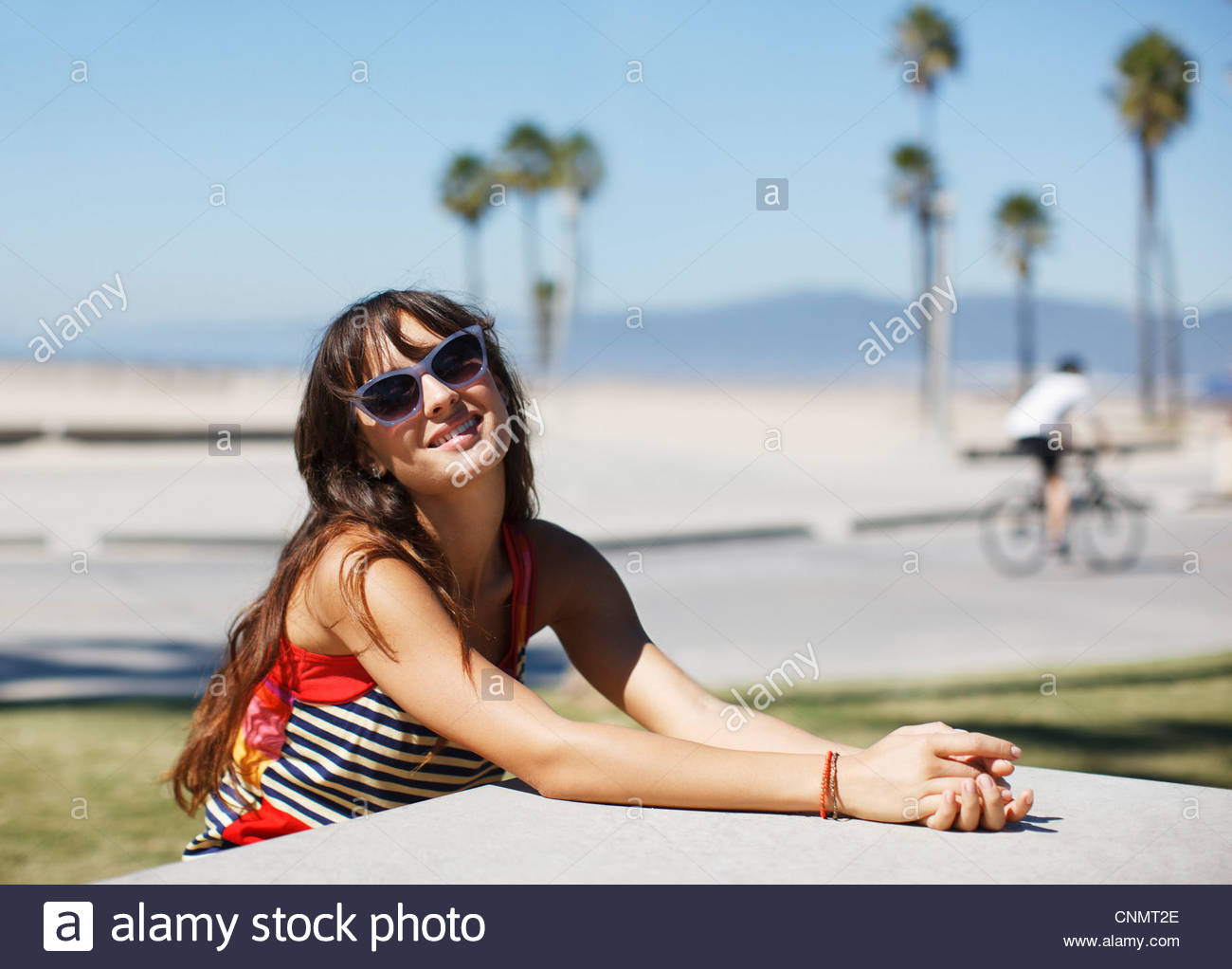 Woman sitting at table in park - Stock Image