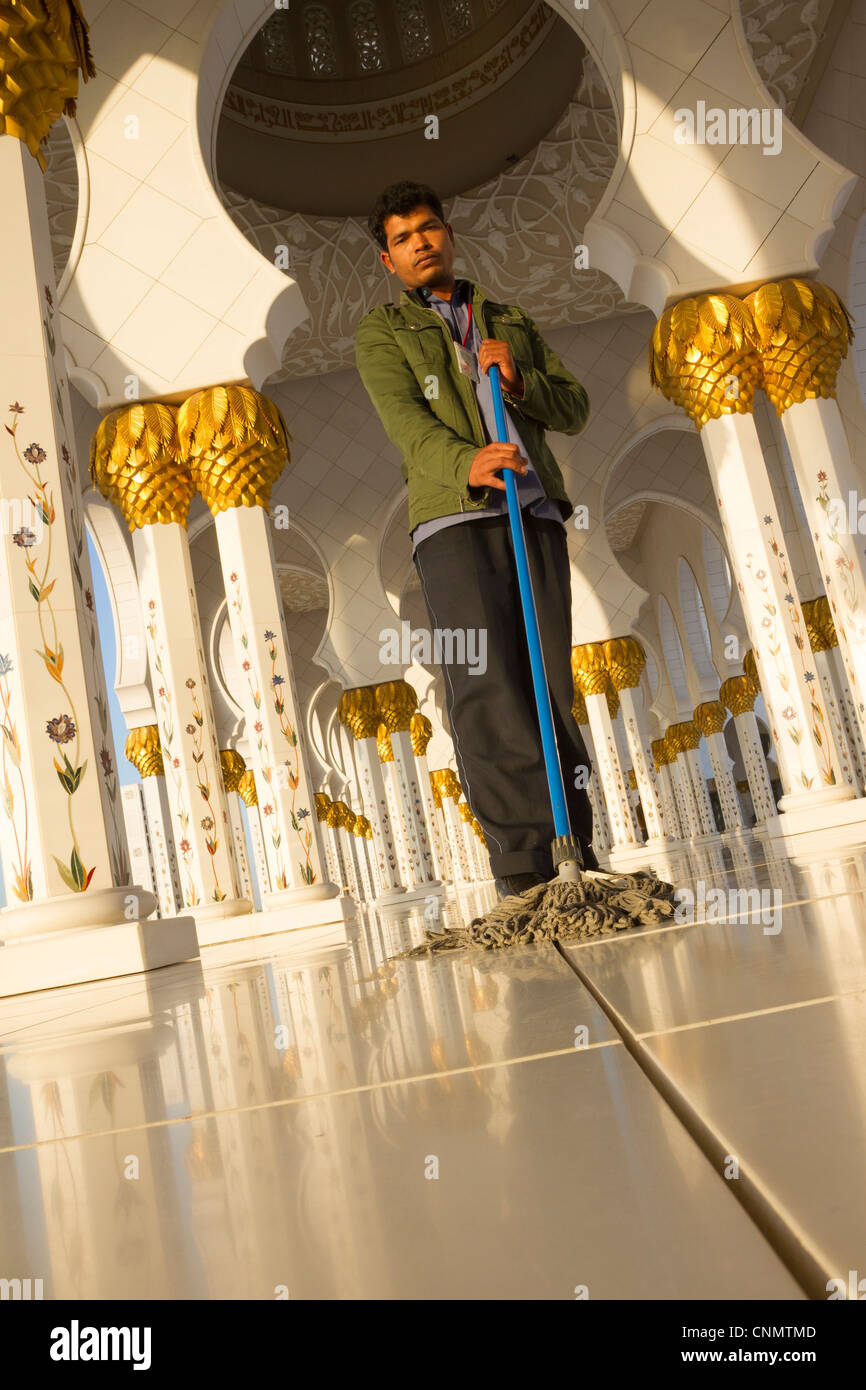 Migrant worker from India mopping floors at the Sheikh Zayed Grand Mosque in Abu Dhabi, UAE - Stock Image