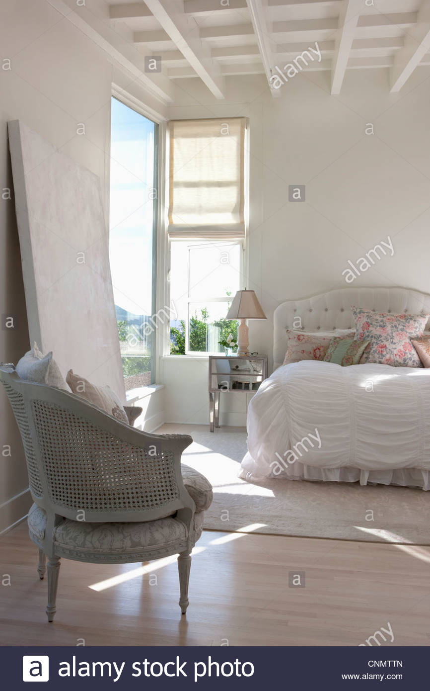 Chair and bed in ornate bedroom - Stock Image