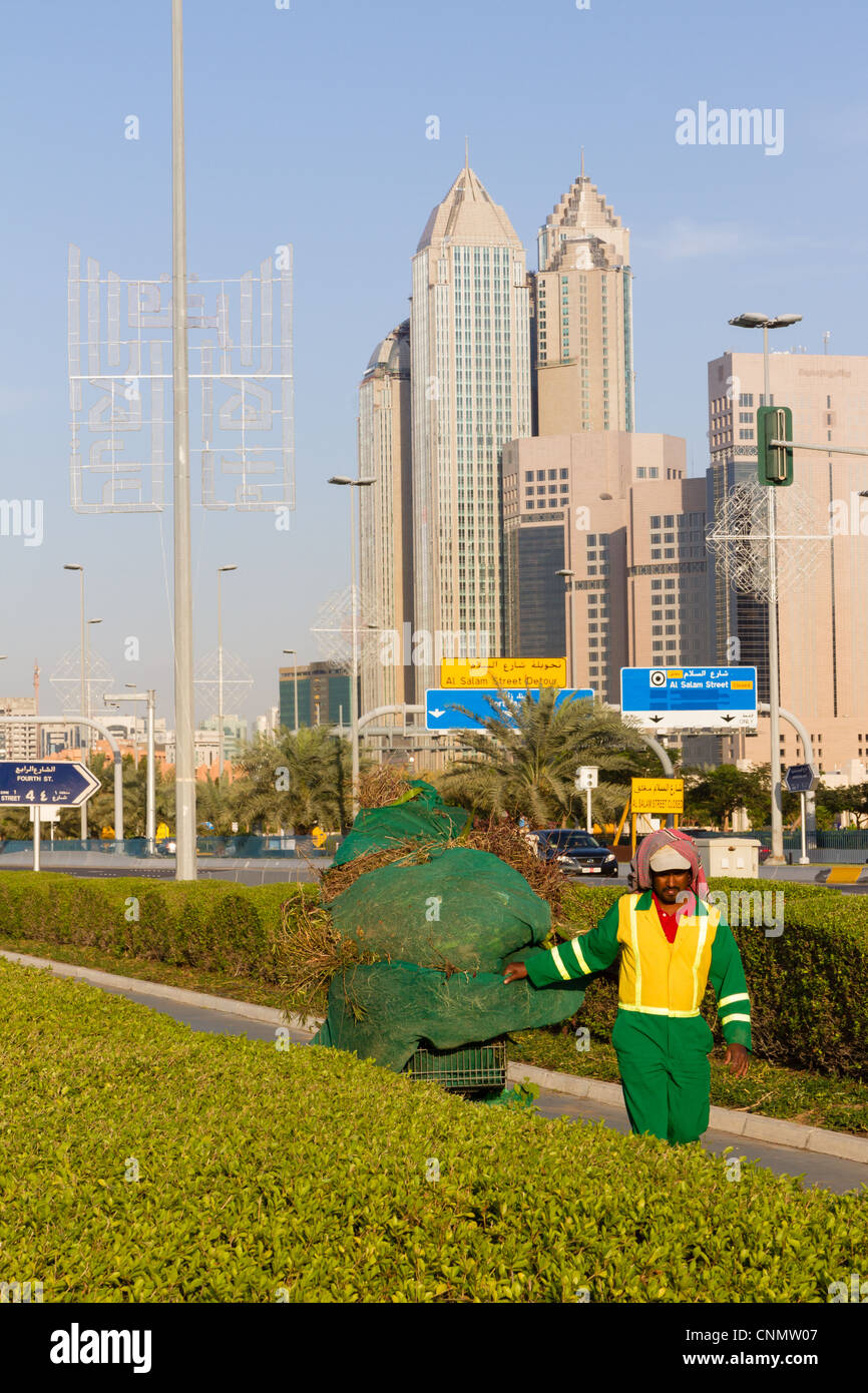 Migrant worker doing garden maintenance along the Corniche in Abu Dhabi, UAE - Stock Image