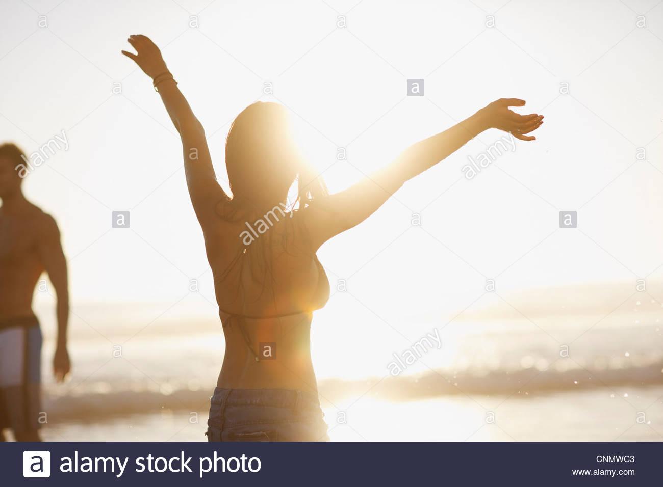 Woman in bikini cheering on beach - Stock Image