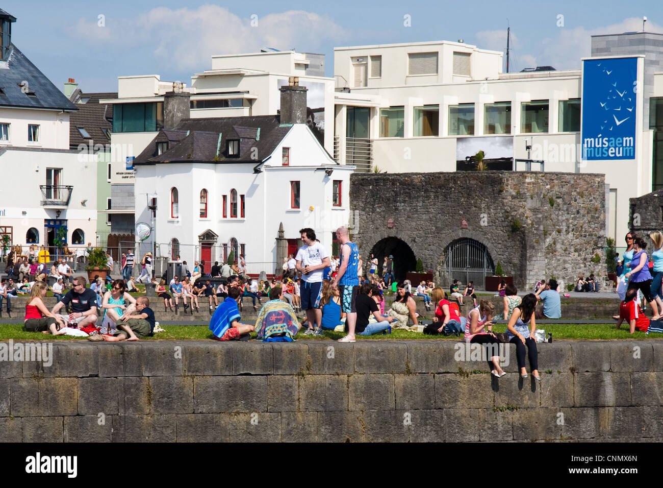 Crowds enjoying the sun at the Spanish Arch quays in Galway City Ireland - Stock Image