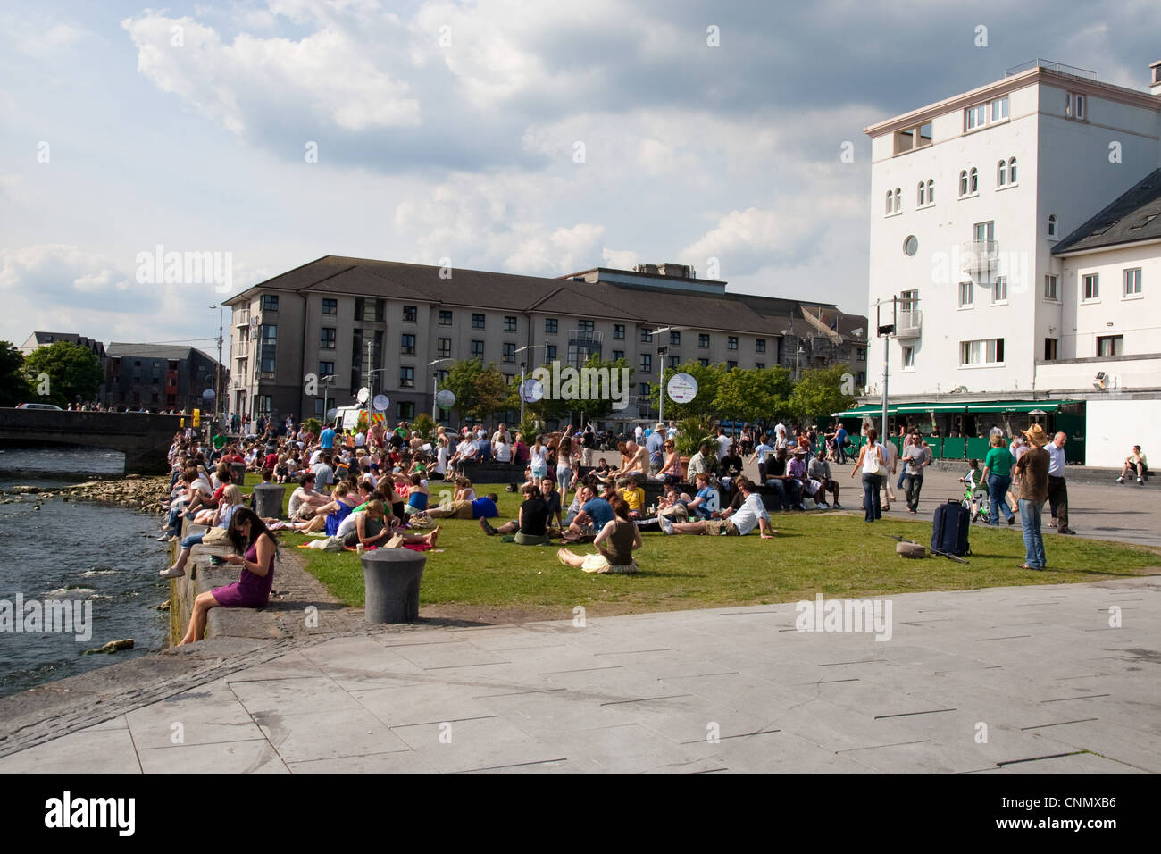 Crowds enjoying the sun at the Spanish Arch in Galway - Stock Image