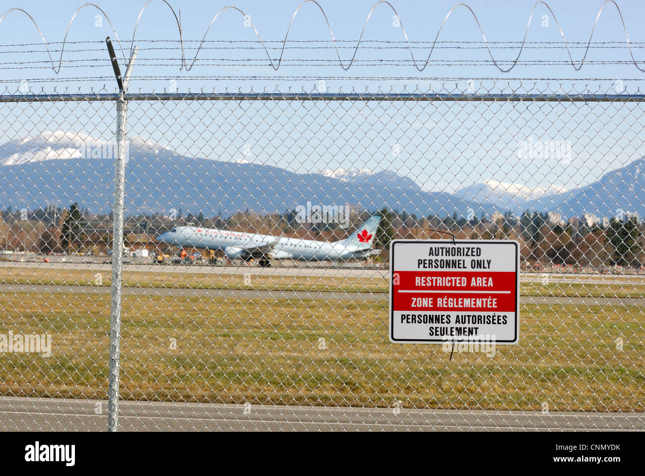 Restricted area sign posted on a security fence at the Vancouver international Airport - Stock Image