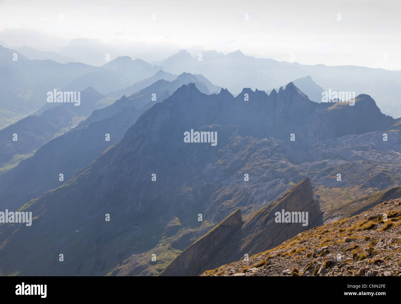 high alpine ragged sharp mountain top ranges disapear in misty distance, Switzerland - Stock Image