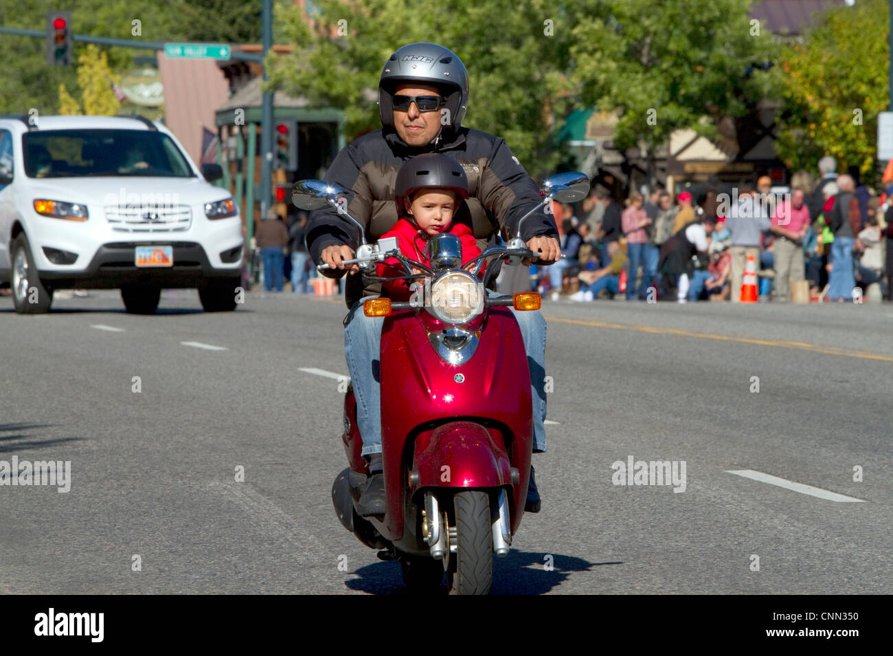 Father and son riding a scooter a the Trailing of the Sheep Parade on Main Street in Ketchum, Idaho, USA. - Stock Image