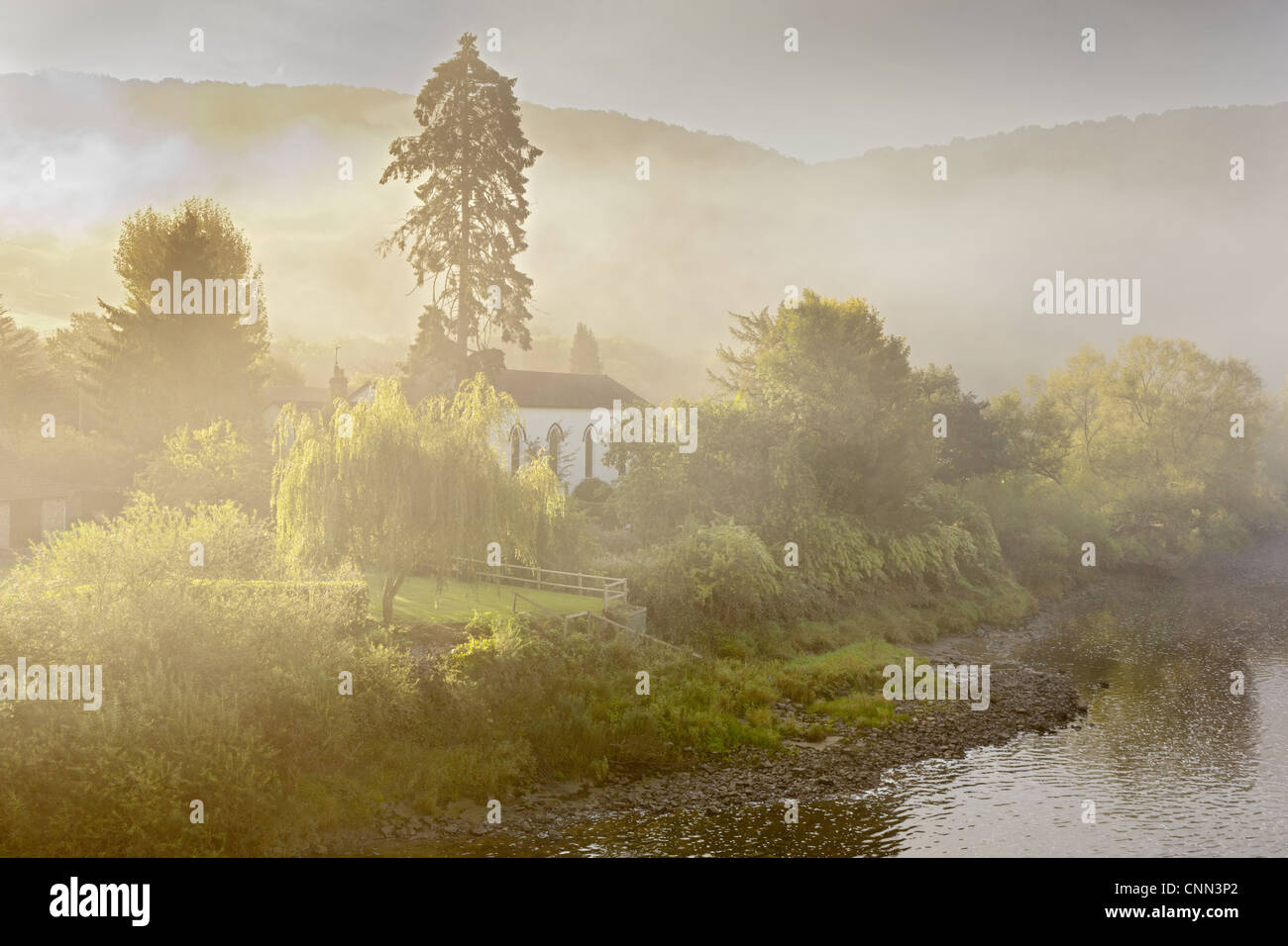 View church on riverbank in mist at dawn Moravian Church Brockweir River Wye Forest Dean Gloucestershire England - Stock Image
