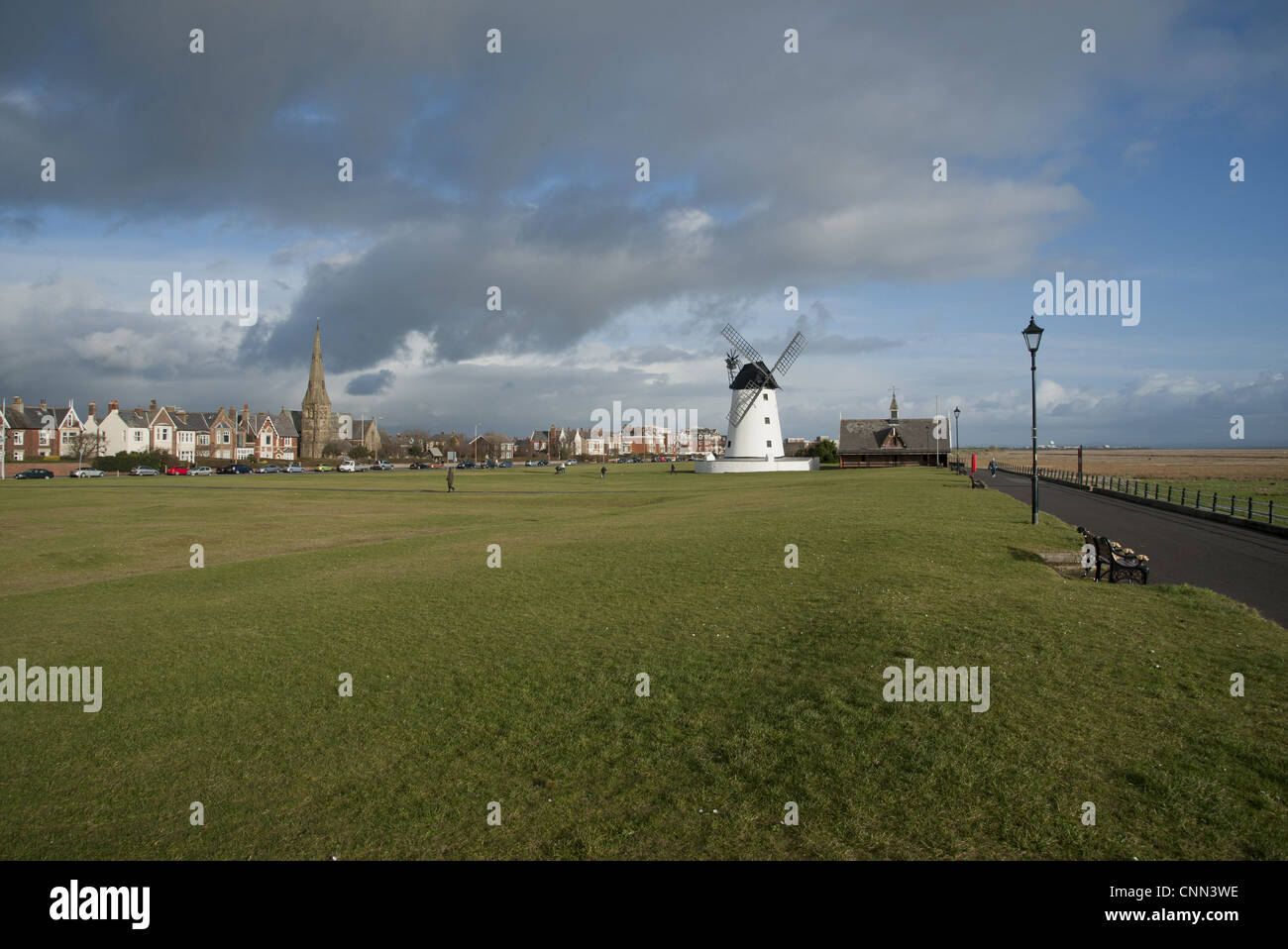 View grass promenade seaside resort town windmill old lifeboat house distance Lytham Windmill Old Lifeboat House - Stock Image