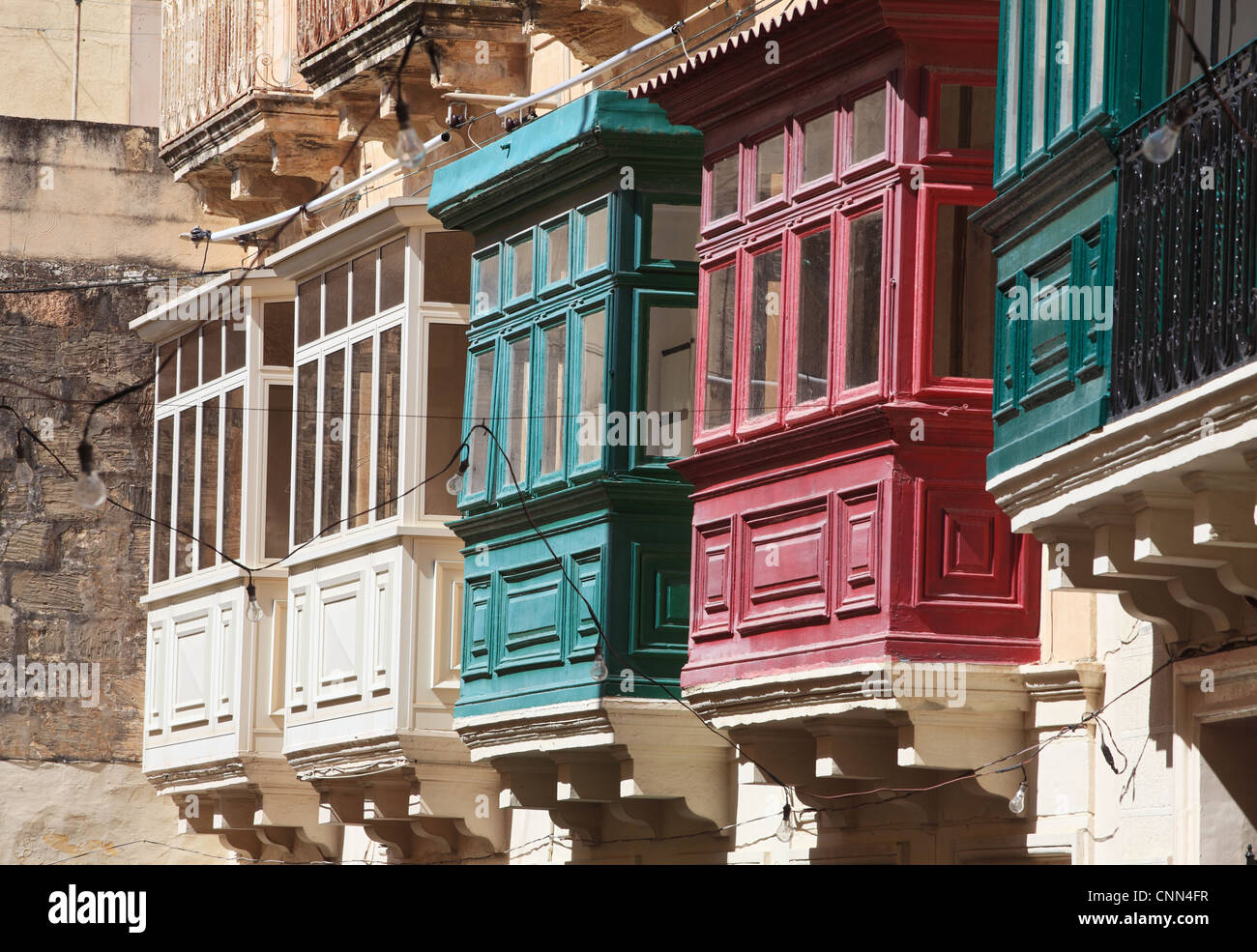 A row of painted traditional bay windows or covered balconies Rabat ,Malta, Europe - Stock Image
