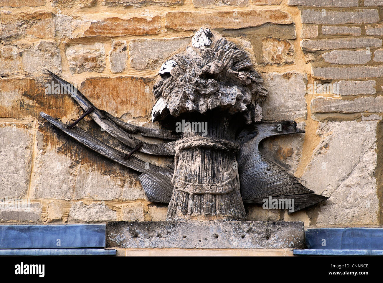 Corn sheaf and plough sign outside the Corn Exchange in Thrapston, Northamptonshire - Stock Image