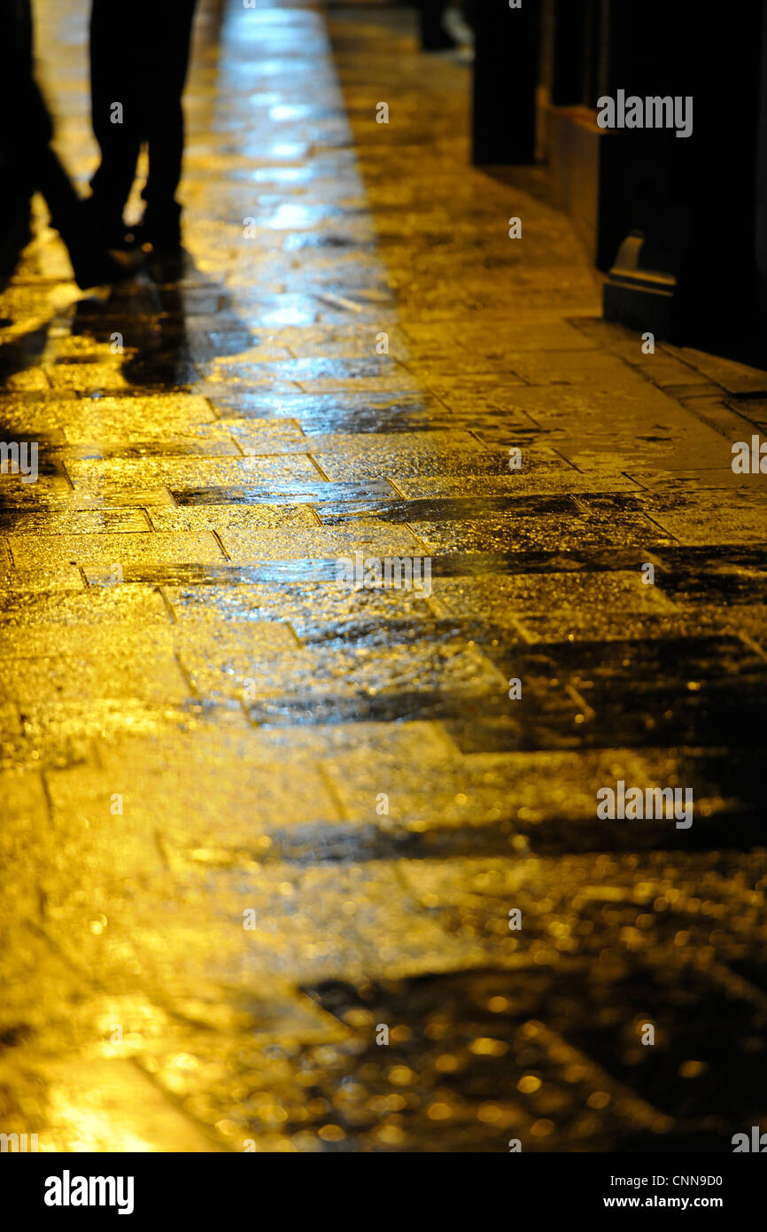 Rain soaked pavements stones at night with yellow light - Stock Image
