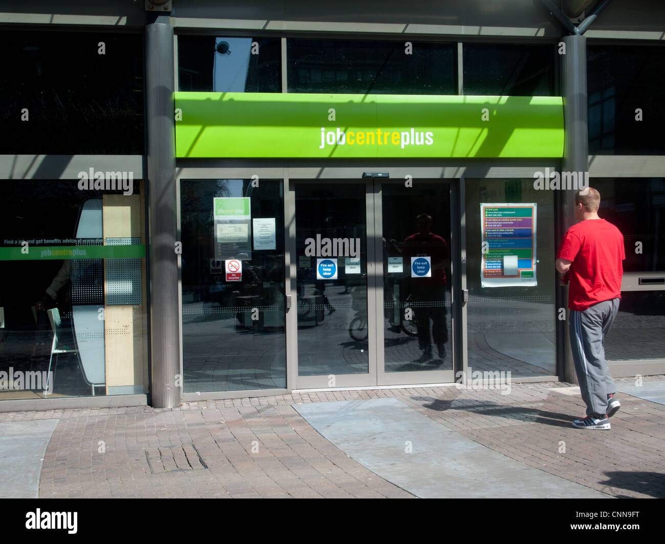 Jobcentre Plus entrance with a customer walking towards the doors - Stock Image