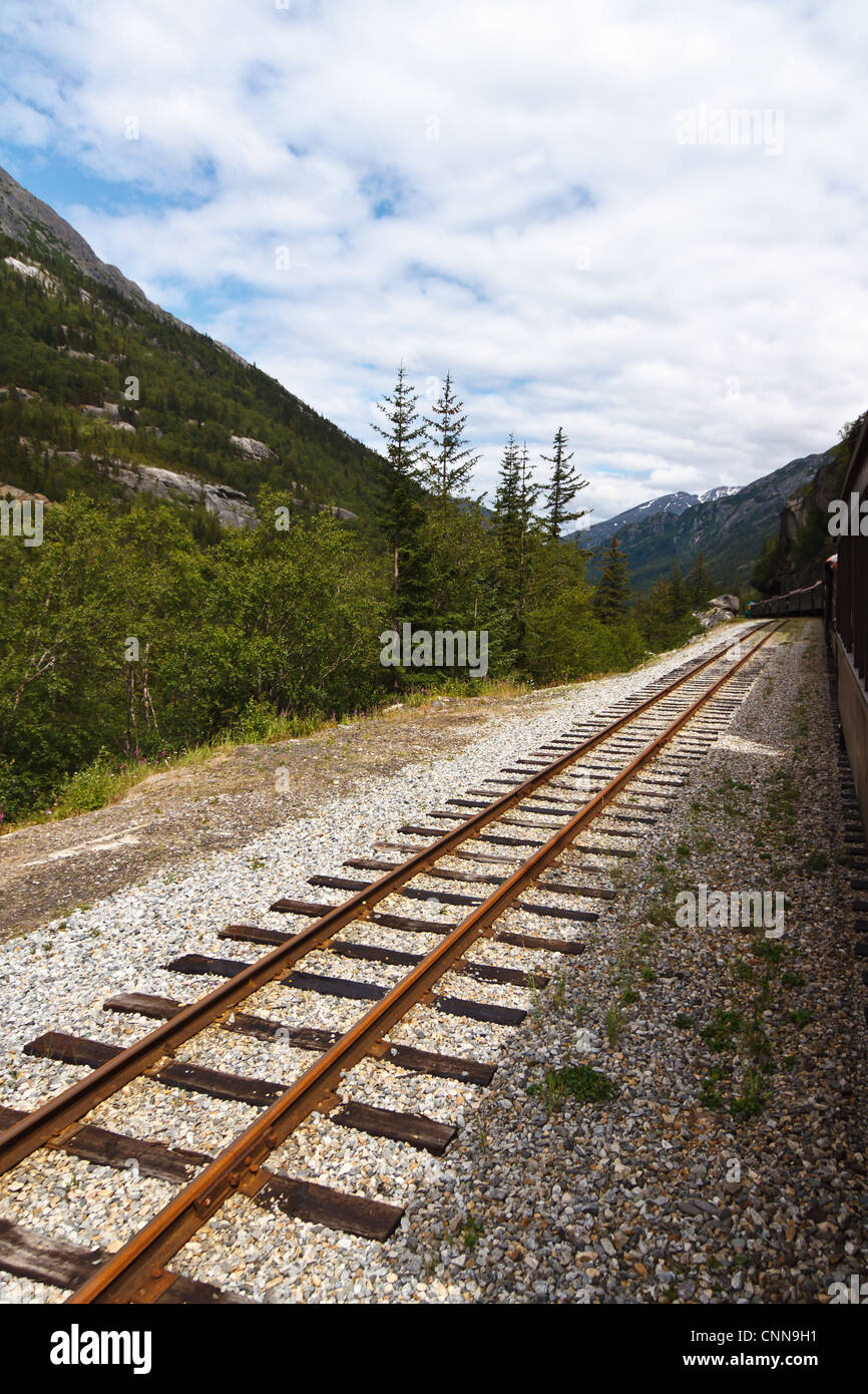 train tracks leading into the distance along side a train - Stock Image