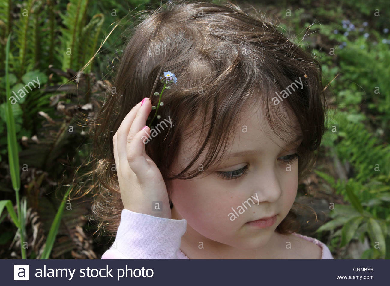 A close up of a little girl with a flower in her hair. - Stock Image