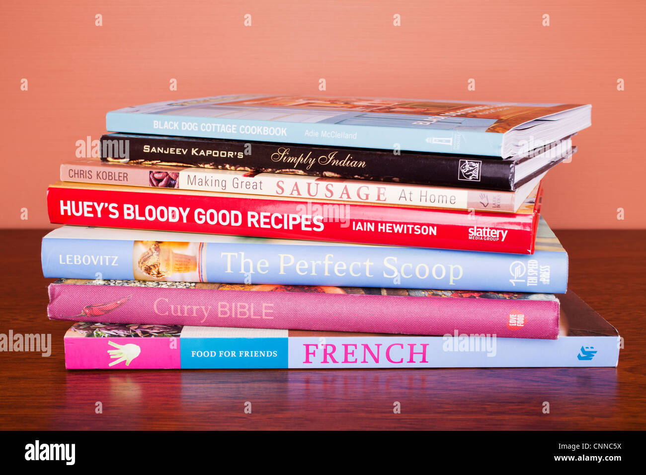 Pile of cookbooks on a table. - Stock Image