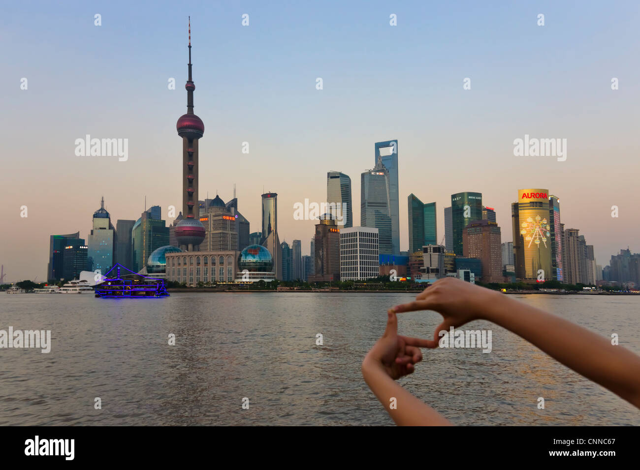 Tourist\'s hand framing a picture of Pudong skyline dominated by ...