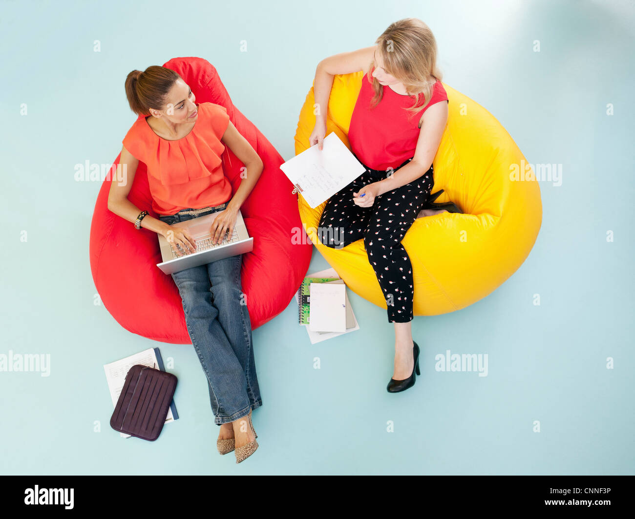 Businesswomen working in bean bag chairs - Stock Image
