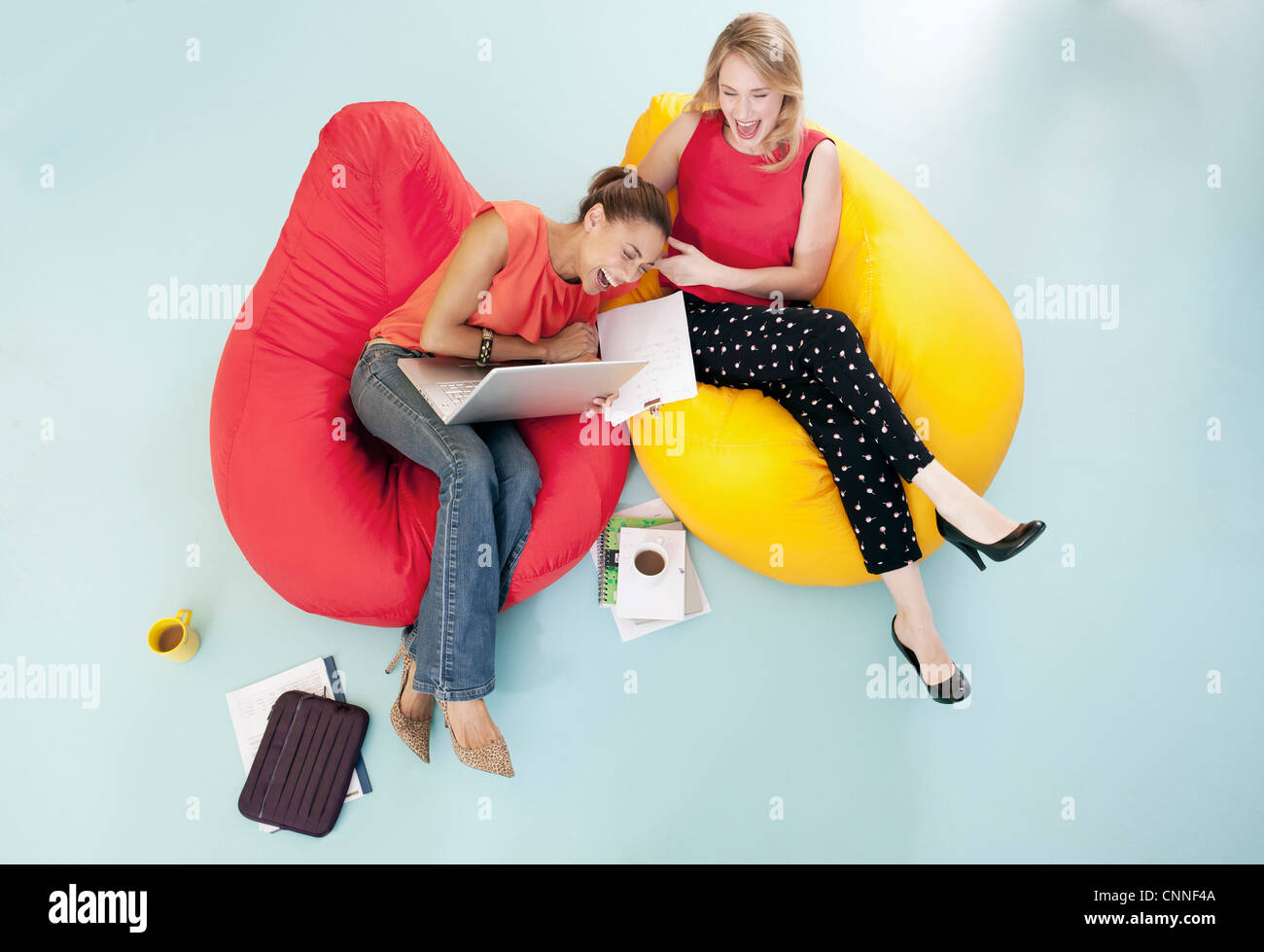 Businesswomen laughing in bean bags - Stock Image