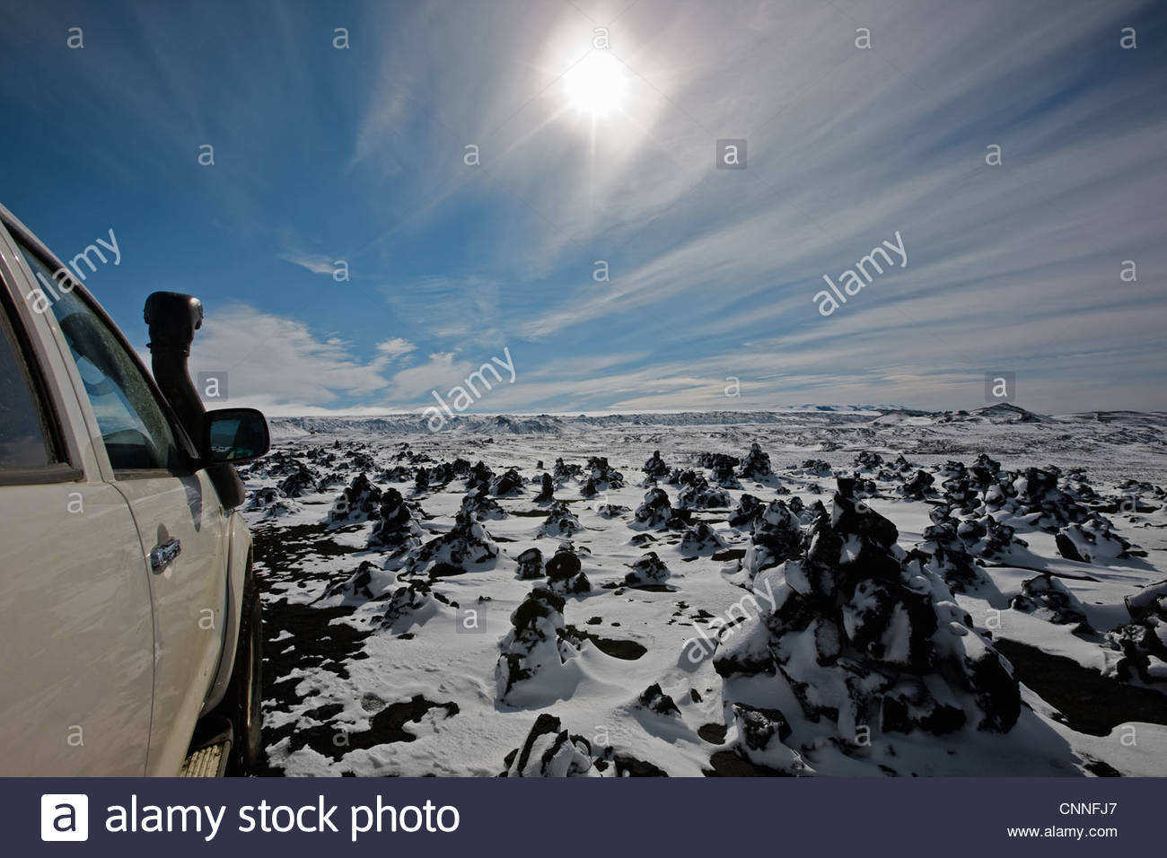 Car parked on snowy rural terrain - Stock Image