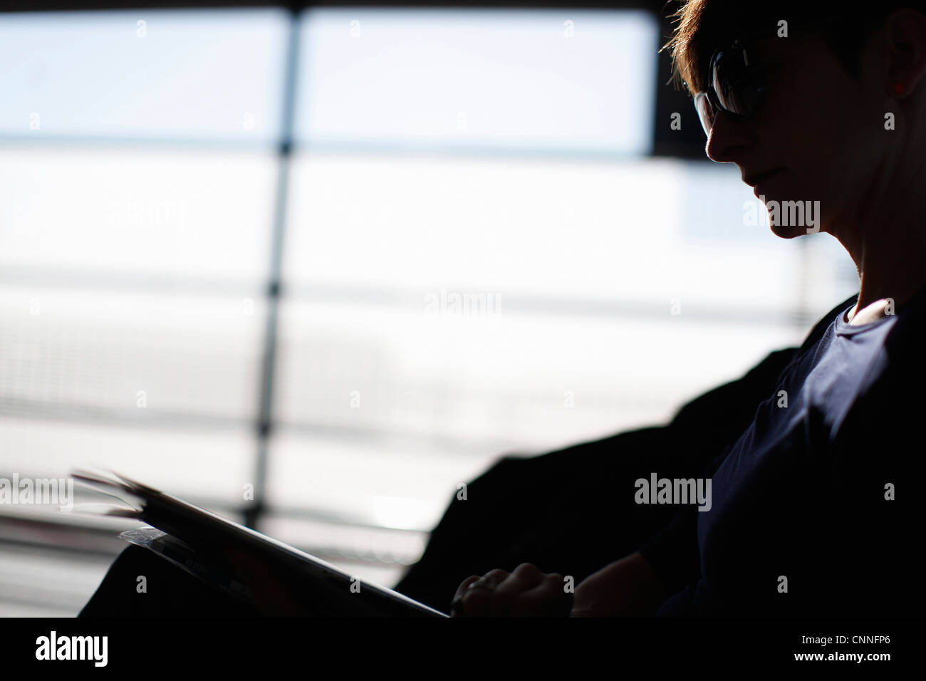 Woman reading magazine in airport - Stock Image