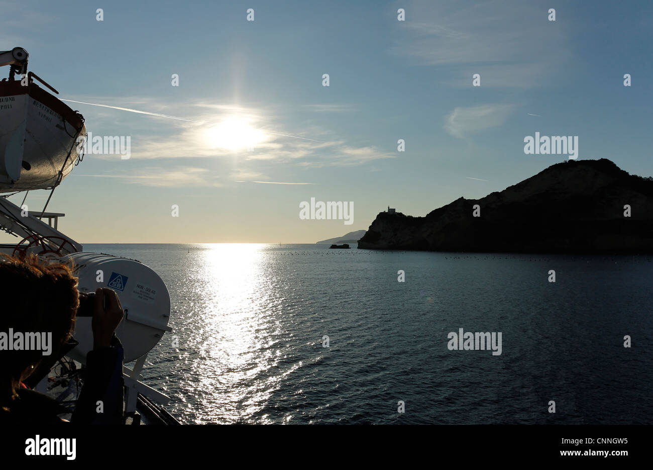 Taking picture on a ferry boat near the lighthouse of Capo Miseno, Gulf of Naples, Pozzuoli, Campania, Italy - Stock Image