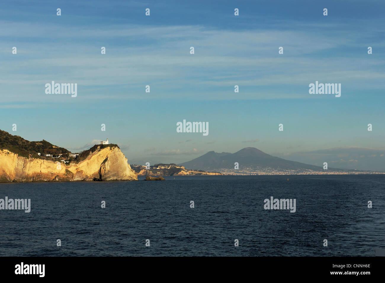 The lighthouse of Capo Miseno with Naples and the Volcano Vesuvio in the background, Gulf of Naples, Pozzuoli, Campania, - Stock Image