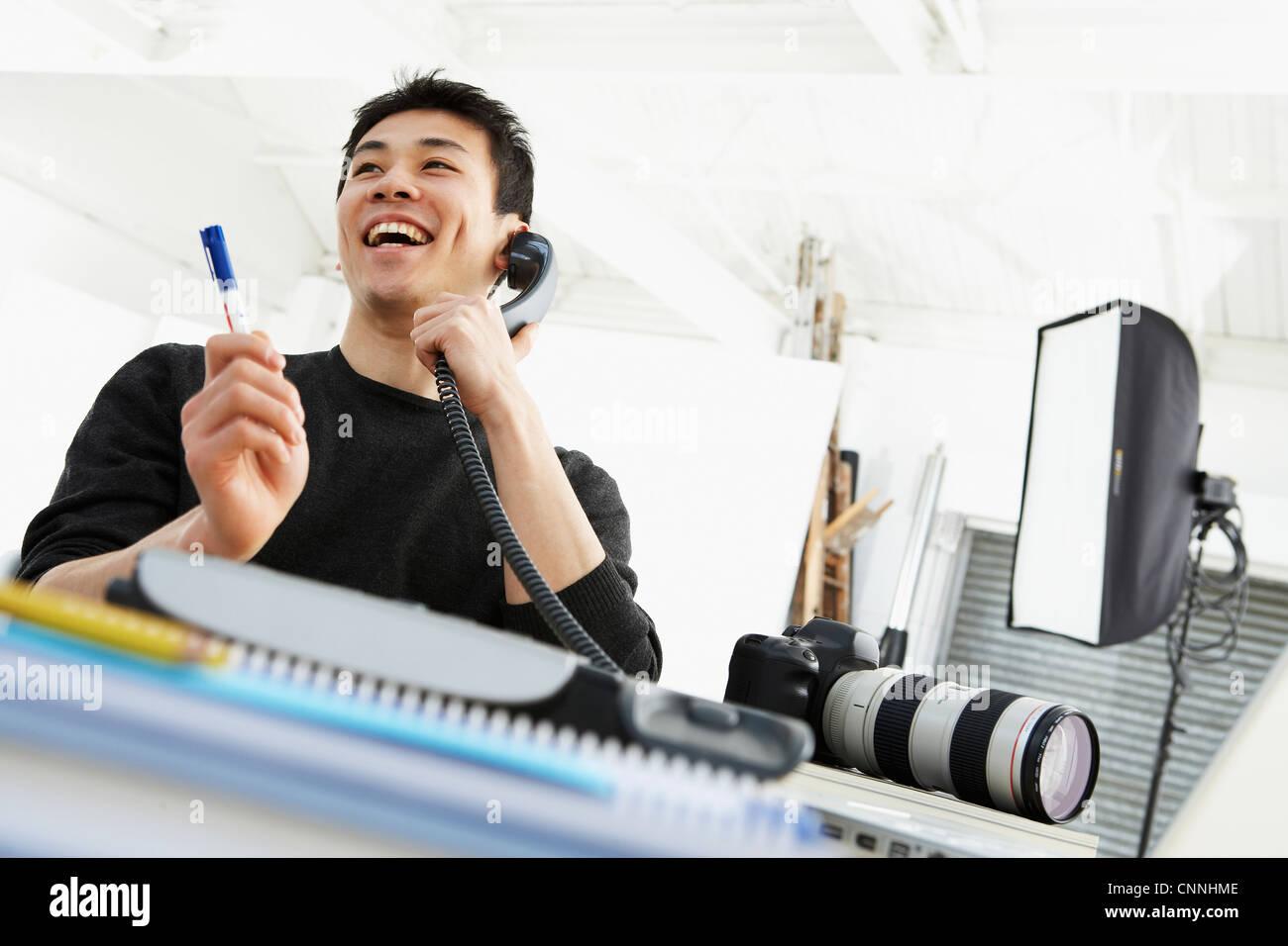 Photographer talking on phone at desk - Stock Image