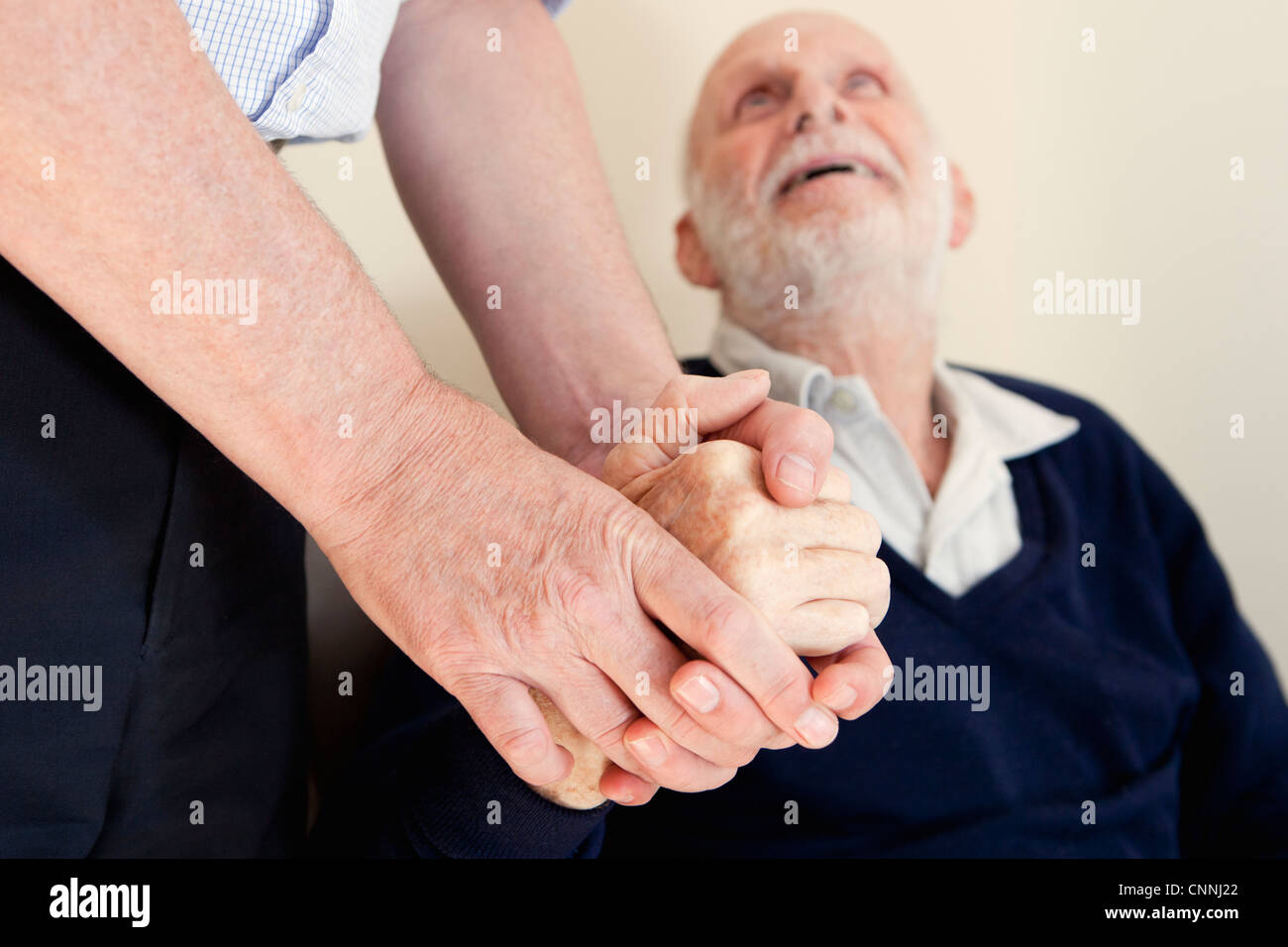 Son patting father's hand - Stock Image