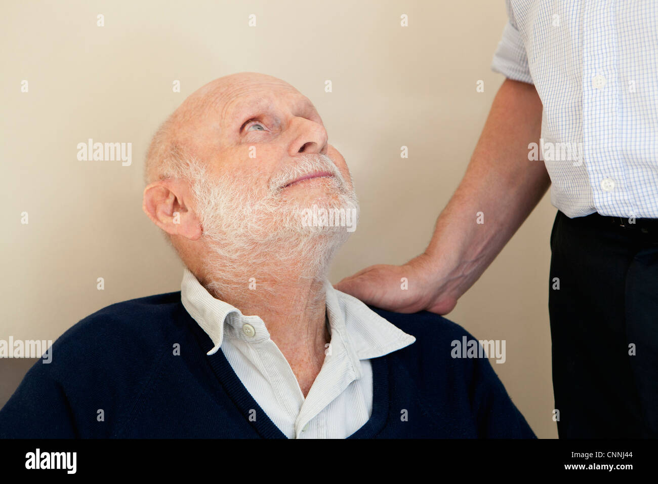 Son patting father's shoulder - Stock Image