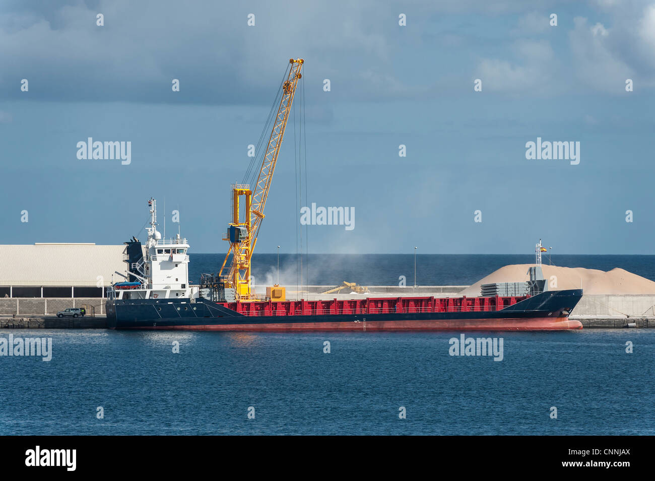 Bulk load being loaded on a vessel in the harbour - Stock Image