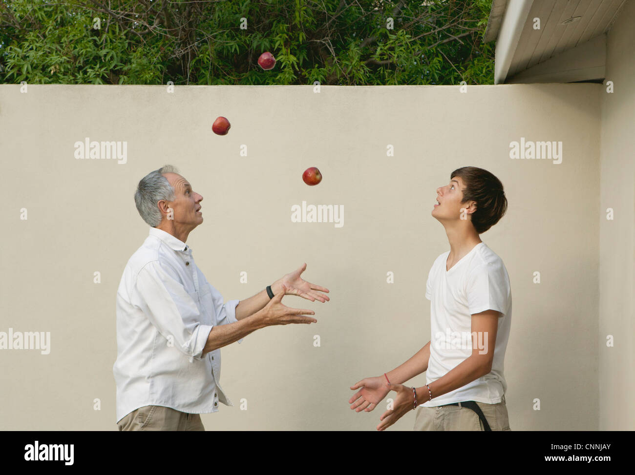 Father teaching son to juggle outdoors - Stock Image