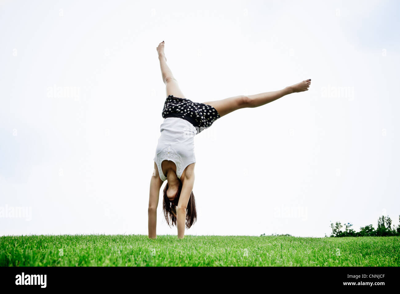 Woman doing cartwheel outdoors - Stock Image