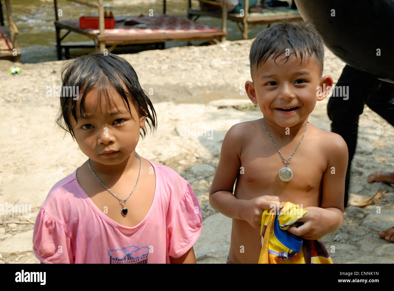 Children throwing cold water at each other on a very hot day on 3/04/2012 in Sangkhaburi Thailand - Stock Image