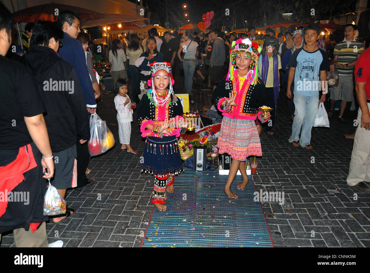 Two small mong hilltribe children dancing in the the sunday market on 14/12/2008 in chiang mai Thailand - Stock Image