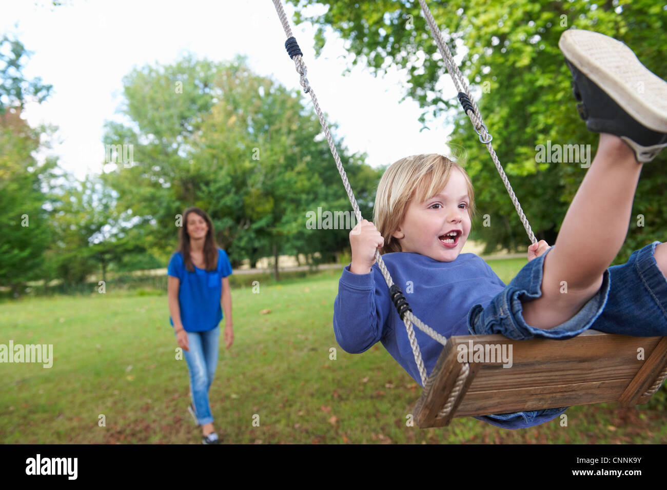 Boy playing on swing in backyard - Stock Image
