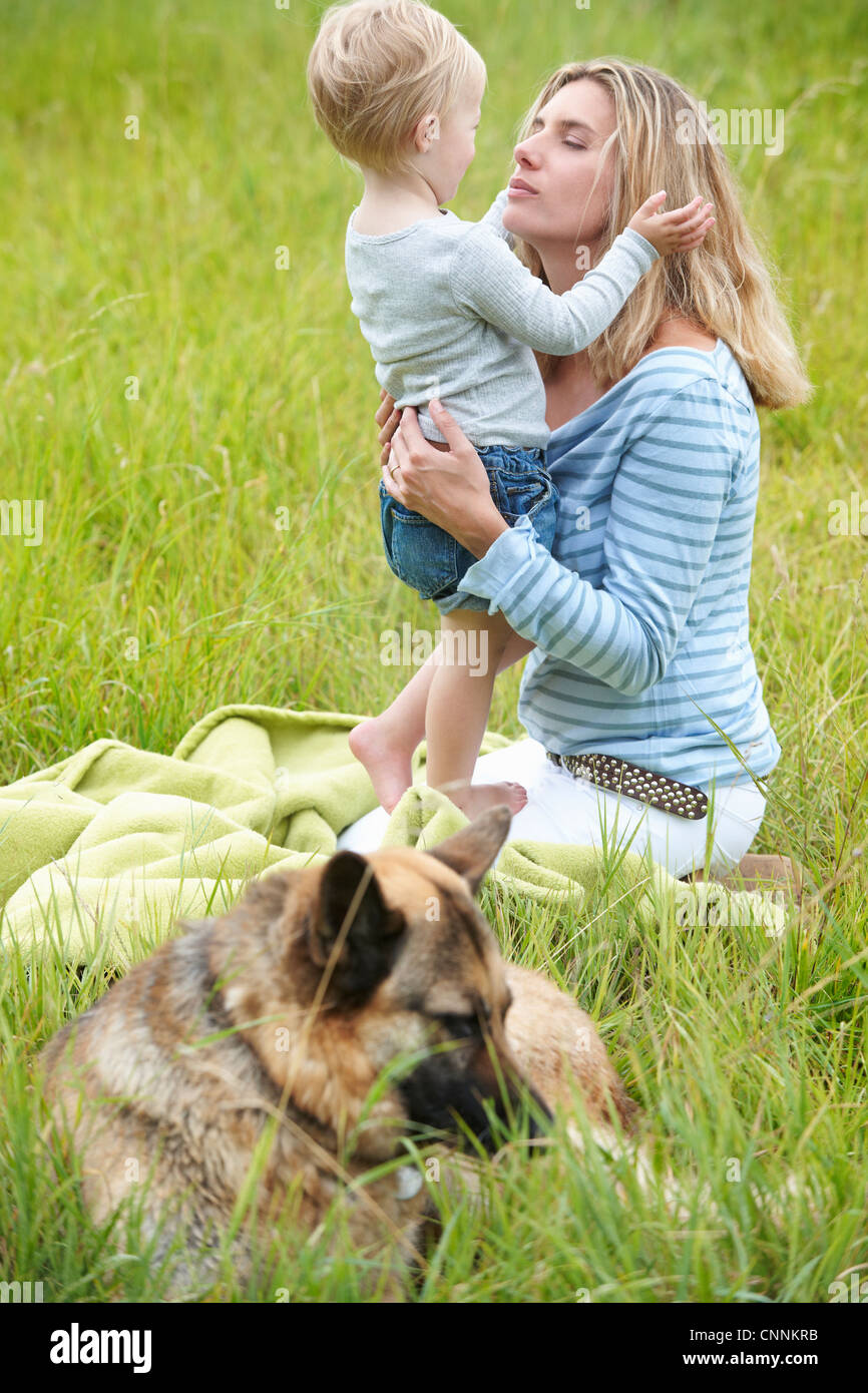 Mother and son sitting in grass with dog - Stock Image