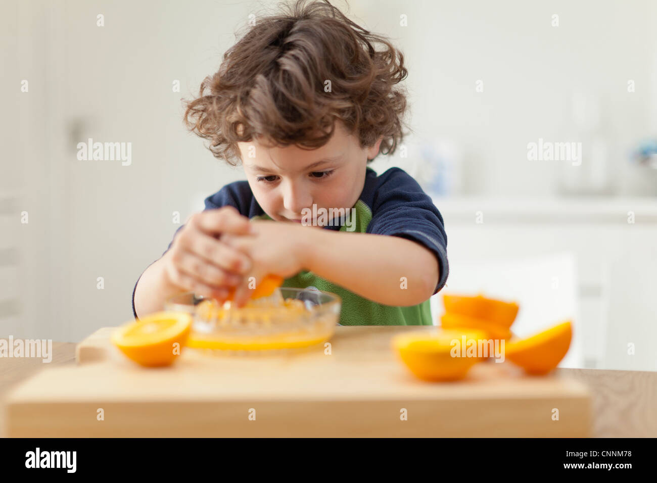 Boy squeezing oranges to make juice Stock Photo