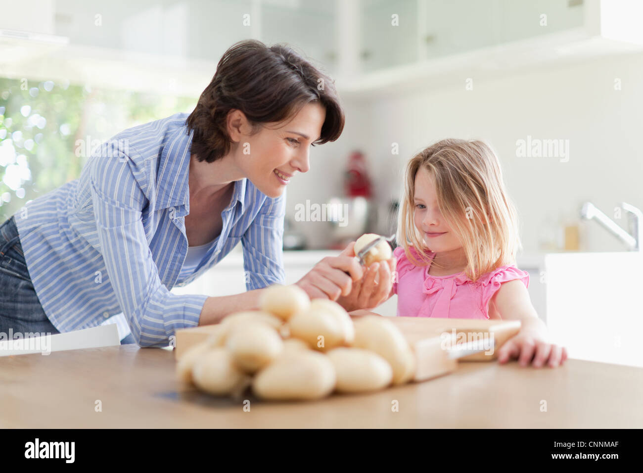 Mother helping daughter peel potatoes - Stock Image