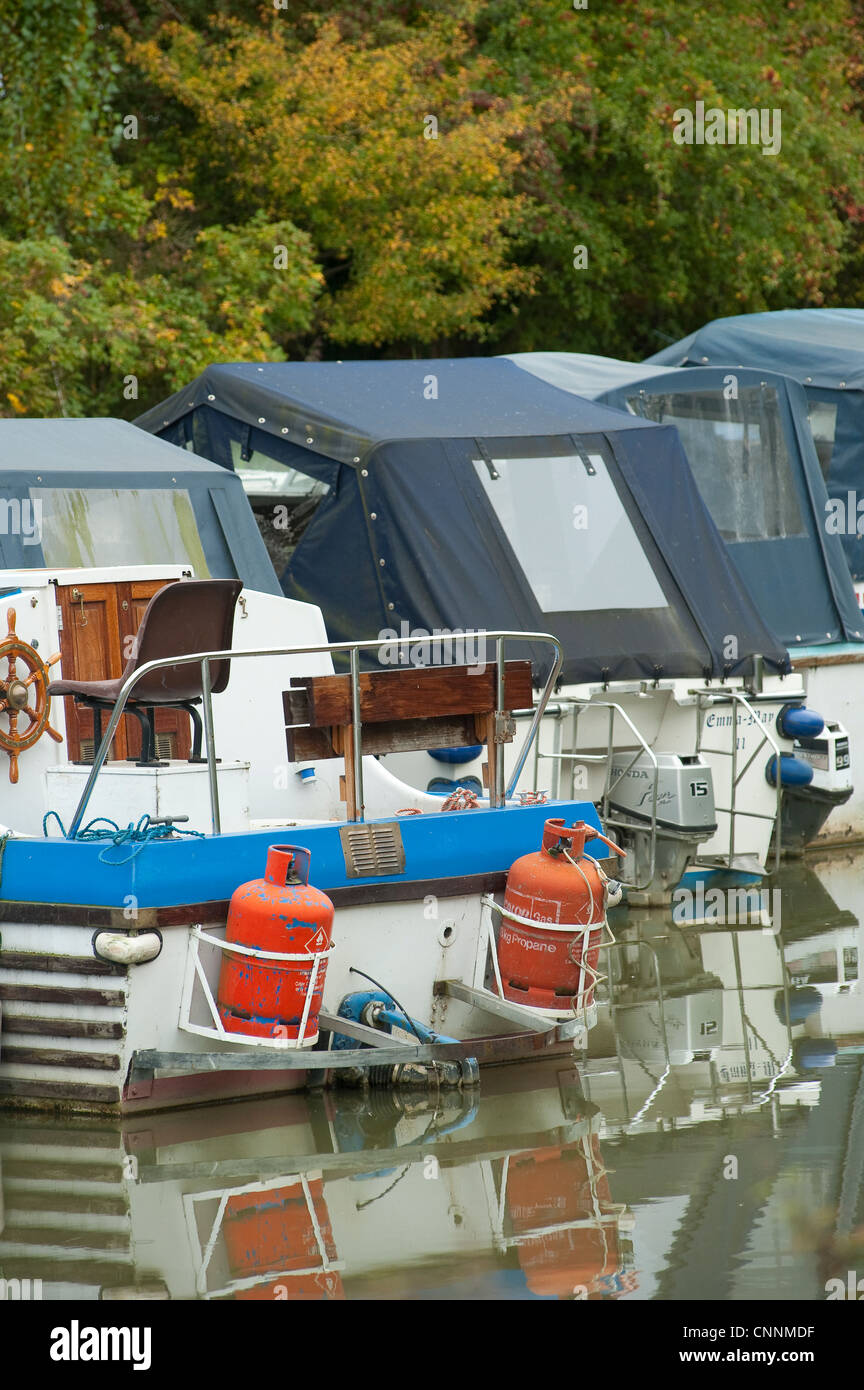 Row of boats moored in a marina with one carrying bottles of propane gas. - Stock Image
