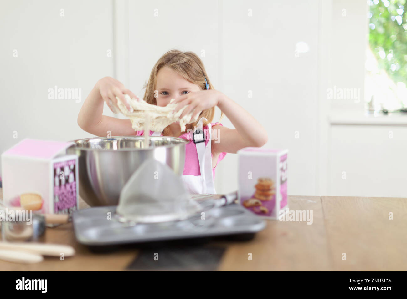 Girl kneading dough in kitchen - Stock Image