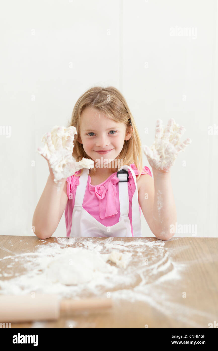 Girl baking with sticky hands in kitchen - Stock Image